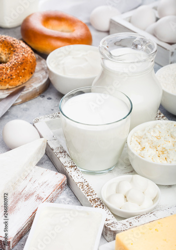 Fresh dairy products in vintage wooden box on white table background. Jar and glass of milk, bowl of sour cream and cheese and eggs. Fresh baked bagel on round chopping board with knife.