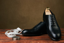 Men's Wedding Shoes On A Brown Wooden Table, Close-up. Business Travel Concept