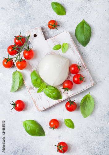 Fresh Mozzarella cheese on vintage chopping board with tomatoes and basil leaf on stone kitchen table background.