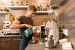 Young male coffee shop worker making coffee with machine