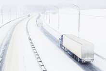 Trucks With Cargo Trailers On The Highway In A Snow Storm. Top View Of A Snowy Asphalt Road In Bad Weather Conditions With Poor Visibility And Slippery Surface. Transportation In A Winter Season
