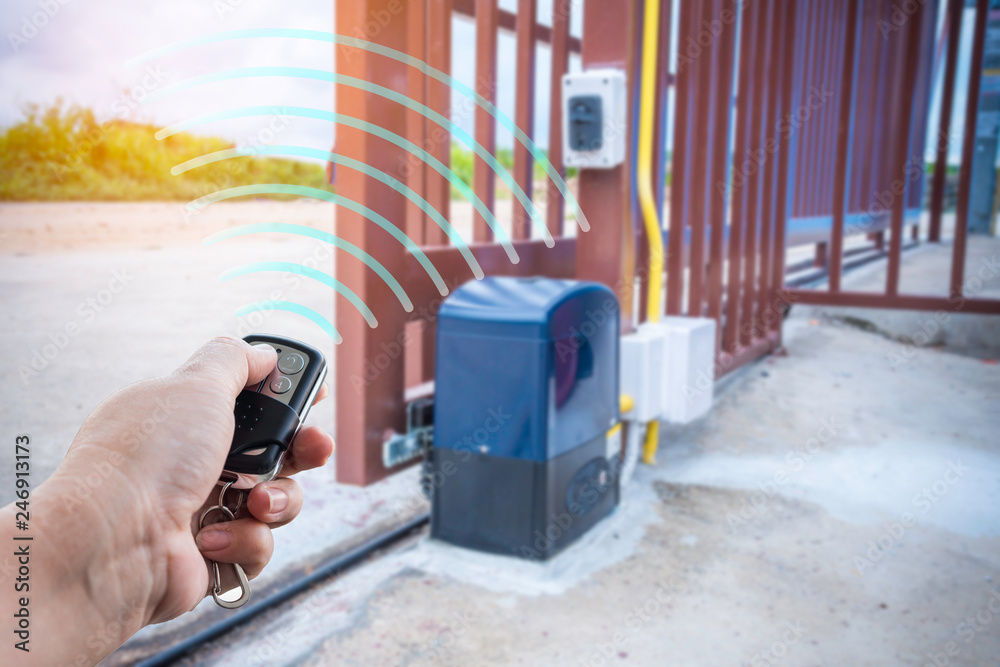Fototapeta Signal of remote control when person open automatic gate at house with sunlight ray