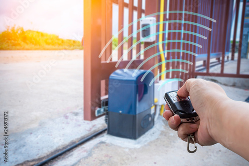 Obraz Signal of remote control when person open automatic gate at house with sunlight ray - fototapety do salonu