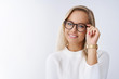Indoor shot of smart and successful female entrepreneur sharing ways to success touching frames checking glasses smiling delighted and accomplished as gazing self-assured at camera against white wall