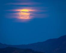Full Moon Rising Over A Desert...