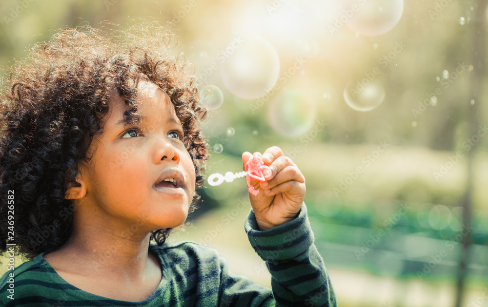 Fototapety, obrazy: Happy little kid blowing soap bubble in school garden. Child outdoor activity concept.