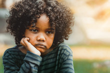 Unhappy Bored Little African American Kid Sitting In The Park. The Boy Showing Negative Emotion. Child Trouble Concept.