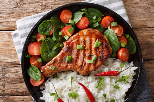 Healthy grilled pork steak with rice and fresh vegetables close-up on a plate. horizontal top view