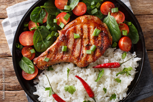 Homemade dinner of grilled pork chop with rice and fresh vegetable salad close-up. horizontal top view
