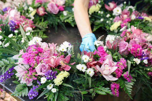 The florist creates a wreath of exotic flowers in pink tones from orchids, roses, and other flowers, herbs.