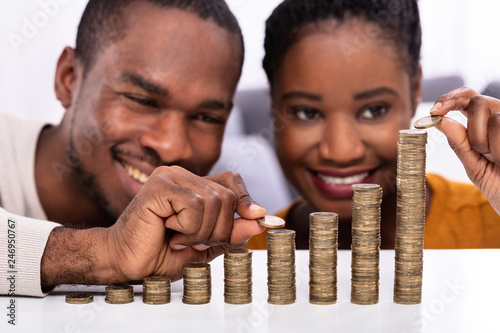 Fotografie, Obraz  Happy Couple Stacking Coins