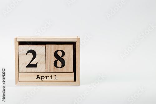Fotografia  Wooden calendar April 28 on a white background