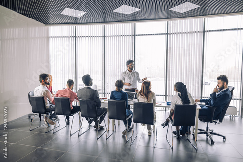 Obraz Achieving best results after annual refresher course. Indian young business mentor conducting a business training while standing in front of people sitting in row at meeting room. - fototapety do salonu
