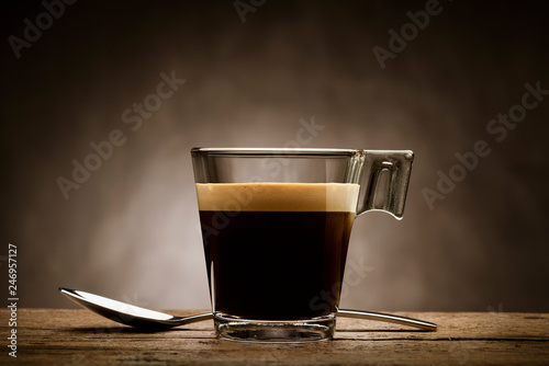 Black coffee in glass cup with teaspoon on wooden table