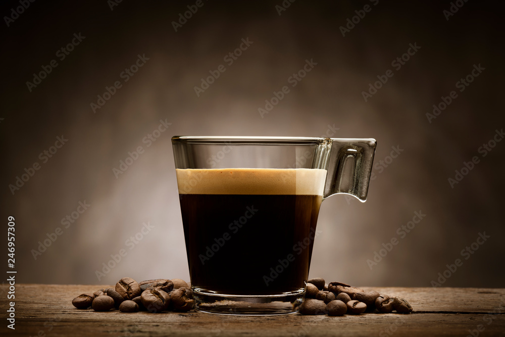 Black coffee in glass cup with coffee beans on wooden table