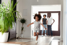 Excited Little Funny African Girl Running Exploring Big Modern House Moving In, Happy Black Parents And Kid Daughter Coming Into New Home, Cute Mixed Race Child Having Fun In Hallway, Family Mortgage