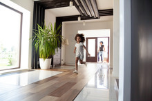 Happy Little Black Girl Running Exploring Big Luxury House Moving In, Parents And Excited Kid Daughter Entering New Home, Cute Mixed Race Child Having Fun Jump In Hallway, African Family Mortgage