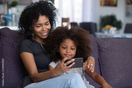 Happy smiling african american mother and little daughter taking selfie on smartphone, mixed race mom and child girl making video call on cellphone, mommy kid watch cartoons using phone app at home