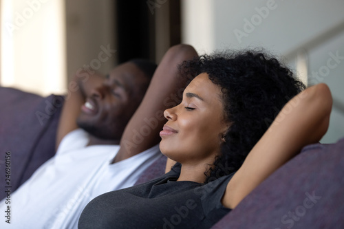 Relaxed african couple enjoying peaceful rest breathing fresh air at home on comfortable couch, happy lazy young black couple having nap leaning on sofa relaxing in living room feel no stress free