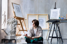 Modern Creative Artist Sculptor Woman Female Creator Sitting At Art Studio Workshop Workplace Exhibition With Wooden Paintbrushes Drawings, Sketches And Gypsum Plaster Sculptures: Horse, Male Portrait