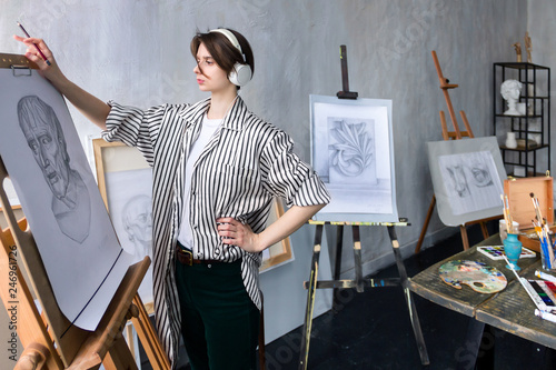 Fotografie, Obraz Modern young freelancer artist sculptor woman in headphone creates new art masterpiece drawing sketch at art workshop workplace studio exhibition with drawings, sketches and gypsum plaster sculptures