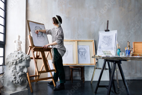 Modern young freelancer artist sculptor woman in headphone creates new art masterpiece drawing sketch at art workshop workplace studio exhibition with drawings, sketches and gypsum plaster sculptures Fototapeta