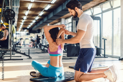 Serious bearded personal trainer helping woman to stretch arms. Woman sitting on the mat, gym interior.