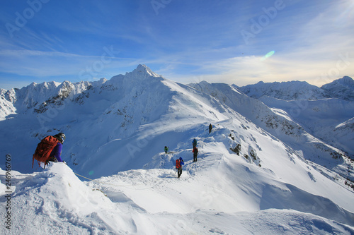 Fotobehang Alpinisme Tied climbers climbing mountain with snow field tied with a rope with ice axes and helmets