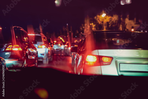 Photo Stands Motor sports Cars in the night traffic jam . Looking behind the cars. Cars are red, yellow night light. Evening traffic jam in Baku on one of streets in the downtown