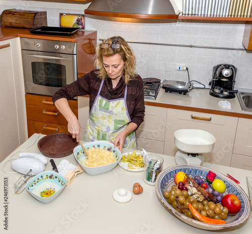 Fotografie, Obraz  Housewife prepares an apple dessert in a messy kitchen