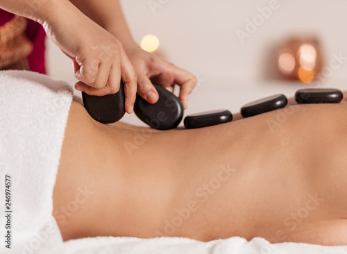 Foto masseur putting black stones on the clien's back