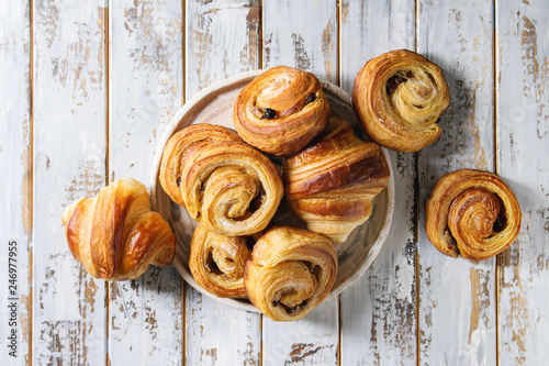 Fotografie, Obraz Variety of homemade puff pastry buns cinnamon rolls and croissant in ceramic plate over white plank wooden background