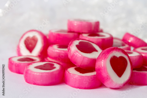Pink and white candys with red hearts on white background