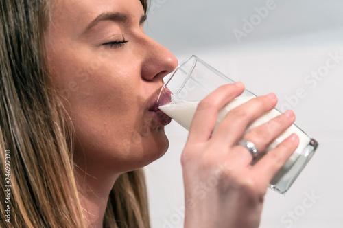 Obraz na plátně Woman drinking milk. woman drinking from a glass of soya milk
