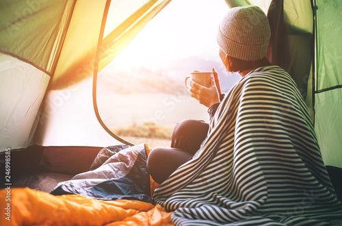 Woman meets cold morning in sitting in touristic tent with cup of ho tea