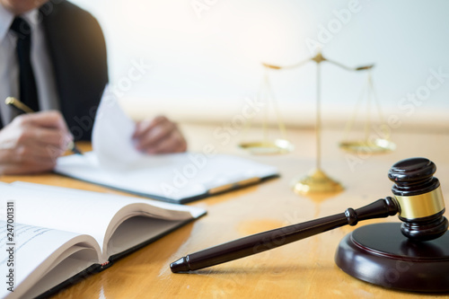 Fotografie, Obraz  Male lawyer working with contract papers and reading law book in a courtroom, justice and law concept while presiding over trial