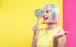Woman in a colorful wig with a giant lollipop on a split yellow and pink background