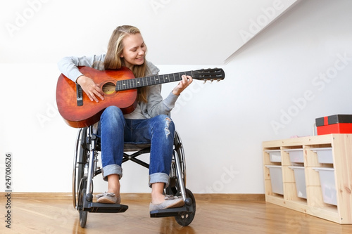 Fotografie, Obraz  Invalid girl on wheelchair plays the guitar in day room.
