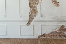 Old Brick Wall With Peeling Plaster, Grunge Background And Wooden Floor