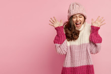 Portrait Of Amazed Happy Woman Raises Hands, Shows Palms, Wears Oversized Knitted Jumper And Hat, Laughs At Something Positive, Isolated Over Pink Background With Empty Space For Your Information