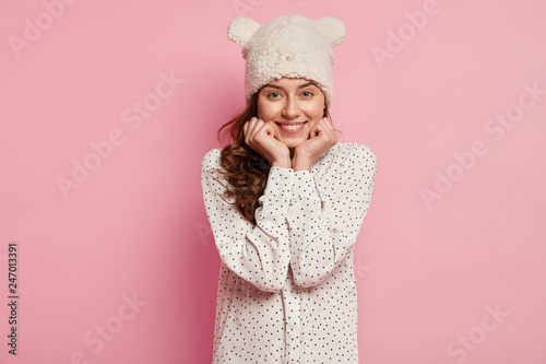 Fotografija  Photo of attractive young European woman keeps hands under chin, has toothy smil
