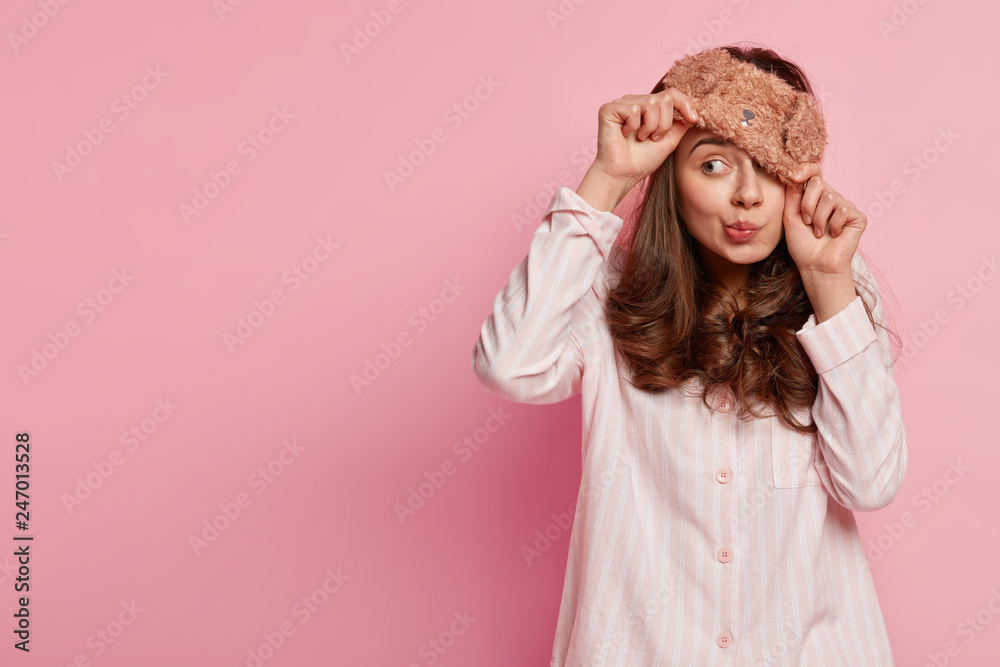 Fototapety, obrazy: Indoor shot of funny young European woman wears eyemask, pyjamas, looks away, poses against pink background with copy space for your promotional content or advertisement. People and rest concept