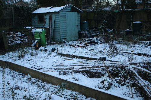 Winter landscape of wooden decaying old shed in allotment garden with raised bed Canvas Print