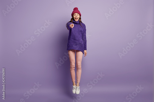 Fotografia Happy woman dressed in fashionable winter clothes, points with fore finger directly at camera, sees something amazing forward, jumps with happiness against purple background