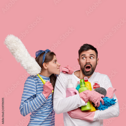 Foto auf Leinwand Akt Vertical shot of dissatisfied woman looks angrily at husband, reproaches of laziness, carries cleaning supplies, isolated over pink background with empty space for your advertisement or text