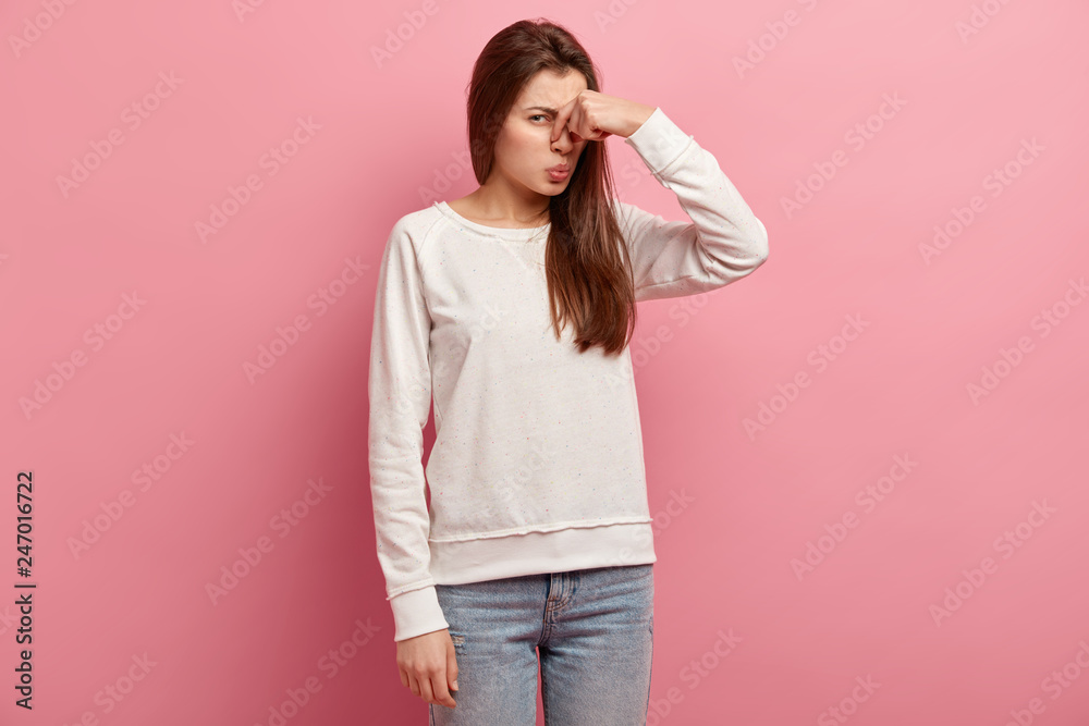 Fototapety, obrazy: Displeased woman covers nose with hand, smells something awful, pinches nose, frowns in displeasure, sees pile of garbage, dressed in casual clothes, isolated over pink background. Bad odour.