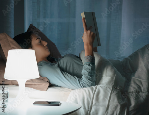 Woman reading a book at night