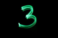Long Exposure, Light Painting Photography.  Single Number Three In A Vibrant Neon Green Colour Against A Black Background
