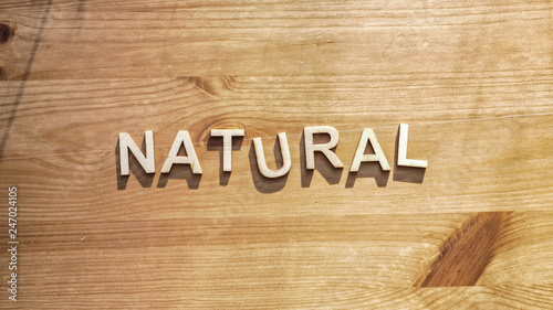 Photo The word natural being spelled by wood letters on a wood surface