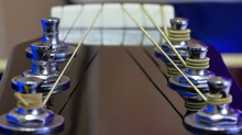 A Close Up Color Image Of A 6 String Guitar Headstock.